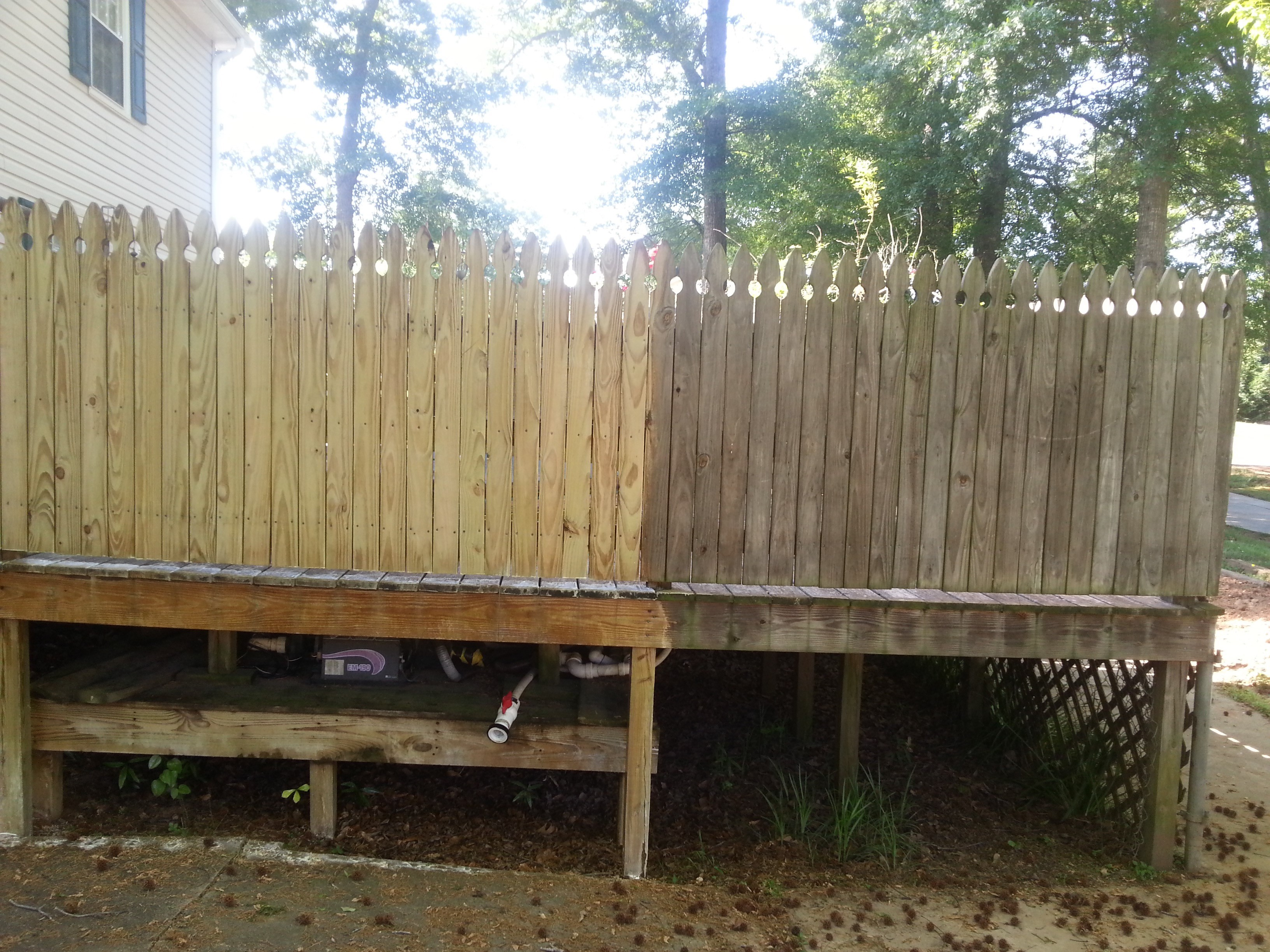 Before and after pressure washing wooden fence.